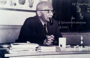 1960 meester Hoekstra in zijn typerende houding met pijp, op een verhoging in de hoek van het lokaal